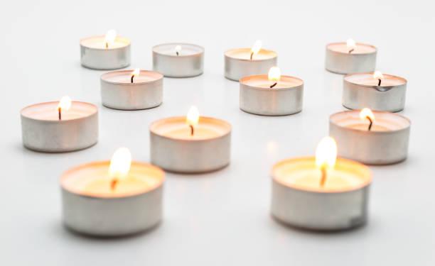 Brennende Paraffinkerzen, Teelicht, liegt auf einem weißen Hintergrund. – Foto