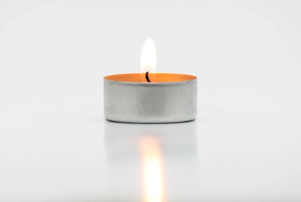 Brennende Paraffinkerzen, Teelicht, liegt auf einem weißen Hintergrund mit einem Beschneidungspfad. – Foto