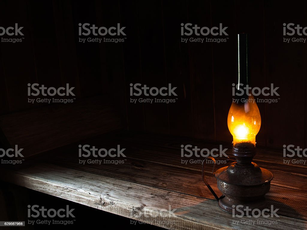 Burning paraffin lamp on the wooden table. stock photo