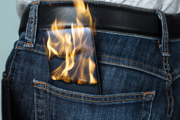 Burning Phone In Jeans Close-up Of A Burning Phone Inside The Back Pocket Of Jeans hot pockets stock pictures, royalty-free photos & images