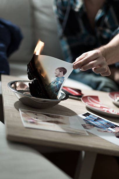 Burning photo after split up Man burning photo with ex-girlfriend after split up former stock pictures, royalty-free photos & images