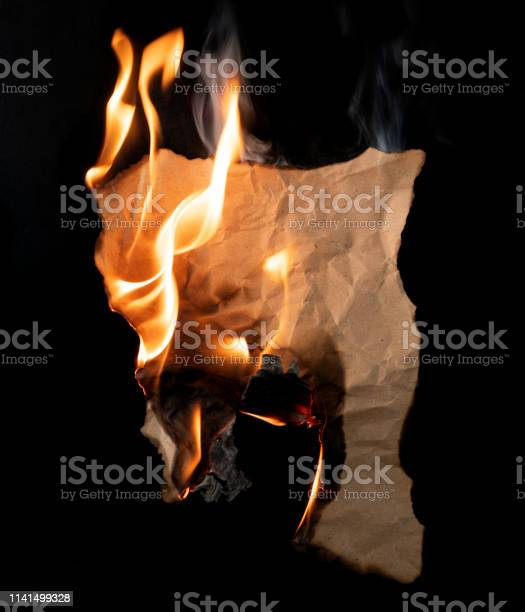 Photo of burning piece of crumpled paper on black background