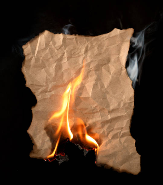 burning piece of crumpled paper on black background burning piece of crumpled paper on black background fire natural phenomenon stock pictures, royalty-free photos & images