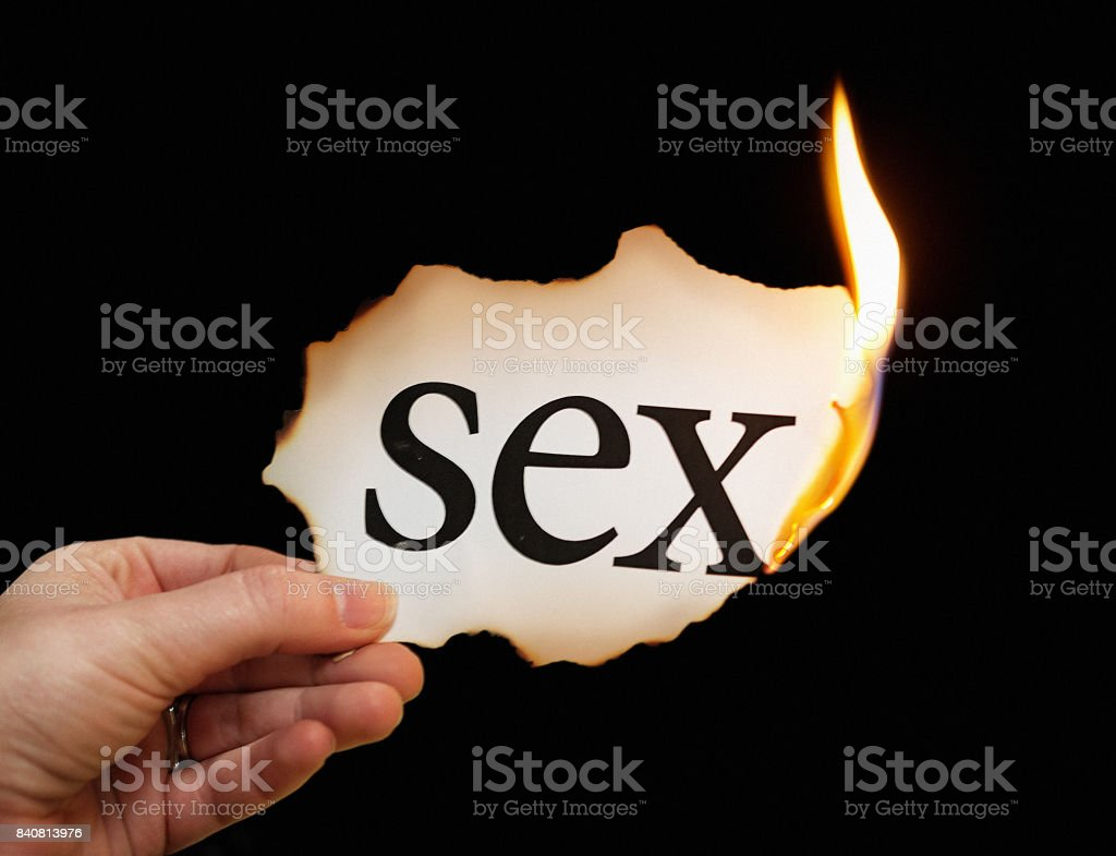 Burning piece of paper labelled 'sex'  held by female hand stock photo