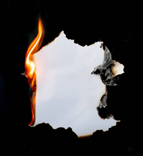 burning piece of  paper on black background - burning stock pictures, royalty-free photos & images