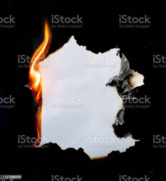 Photo of burning piece of  paper on black background