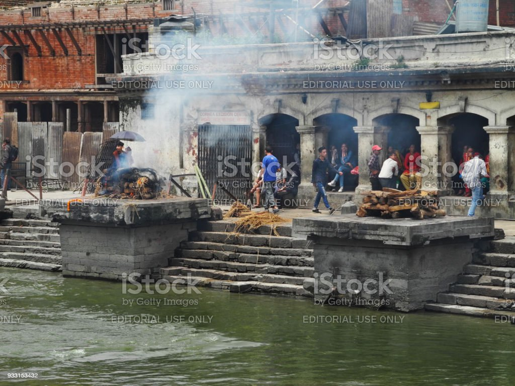 burning pyres and group of nepalese people on cremation at Pashupatinath temple Kathmandu stock photo