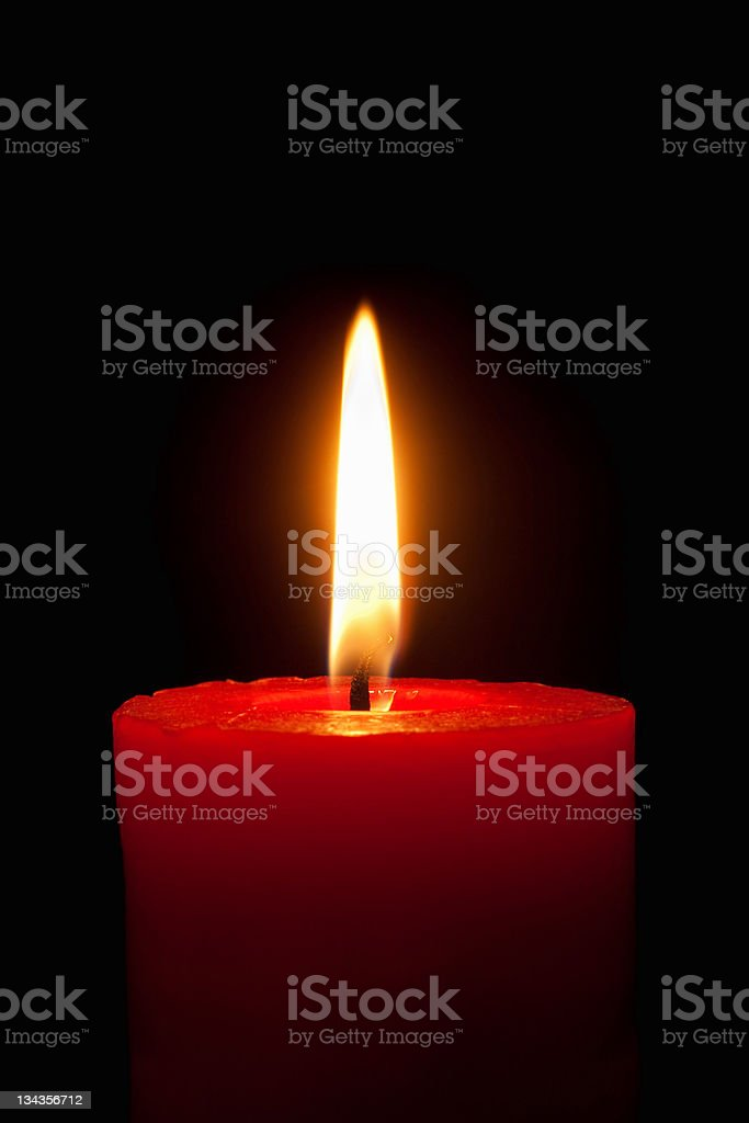 Burning red candle in front of black background royalty-free stock photo