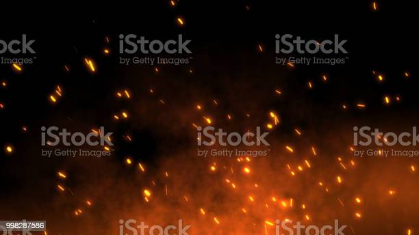 Photo of Burning red hot sparks fly away from large fire in the night sky