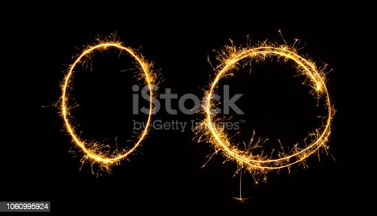 Fireworks zero number close up. Burning sparkler in the shape of oval and circle isolated on black background. Object of Sparklers to overlay a texture for design Holiday postcards, web banners