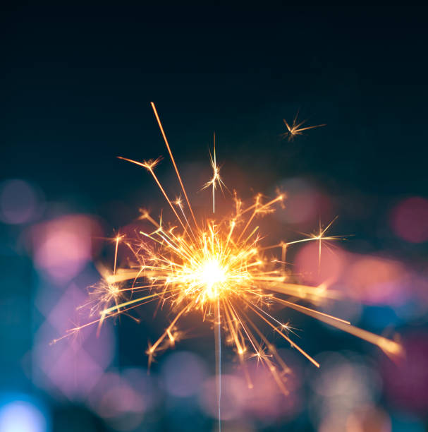 burning sparkler with blurred background - sparkler stock pictures, royalty-free photos & images