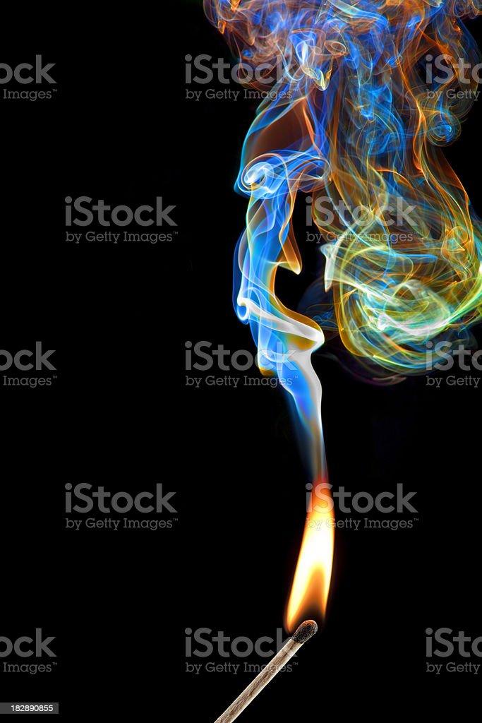 Burning Stick Match With Colorful Smoke on Black Background stock photo