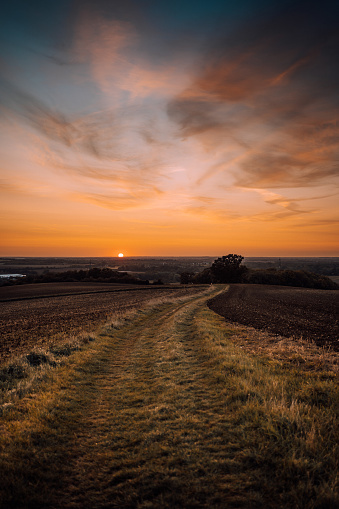 Very red orange autumn sunset across a farmers field in england.