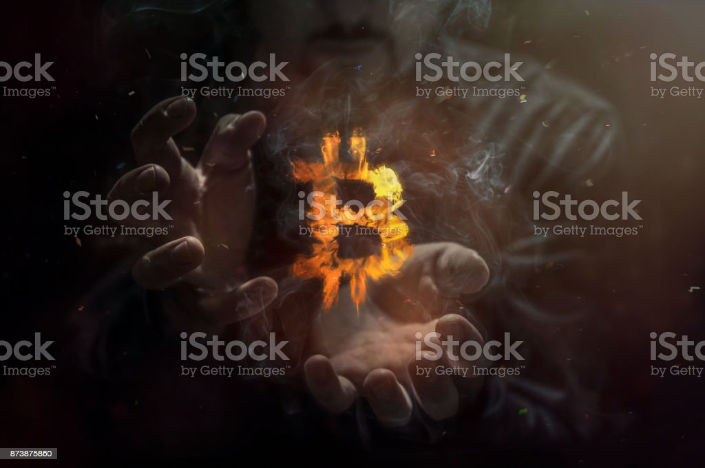 Burning symbol of bitcoin with man in the background. Conception of risk management in money trading at currency market - fotografia de stock