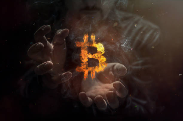 Burning symbol of bitcoin with man in the background. Conception of risk management in money trading at currency market stock photo