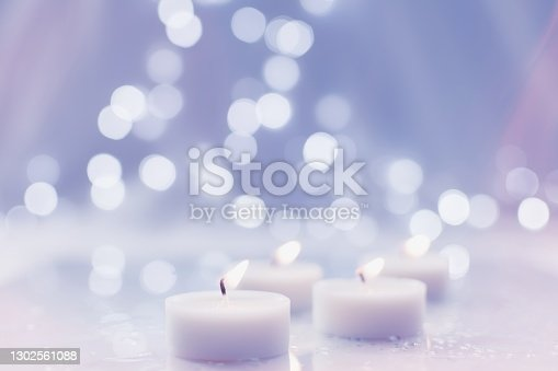 Burning tea light candles with bokeh background