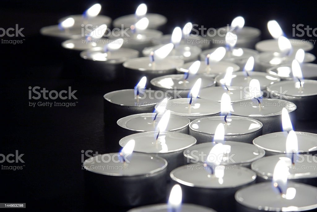 Burning tea lights on black background stock photo