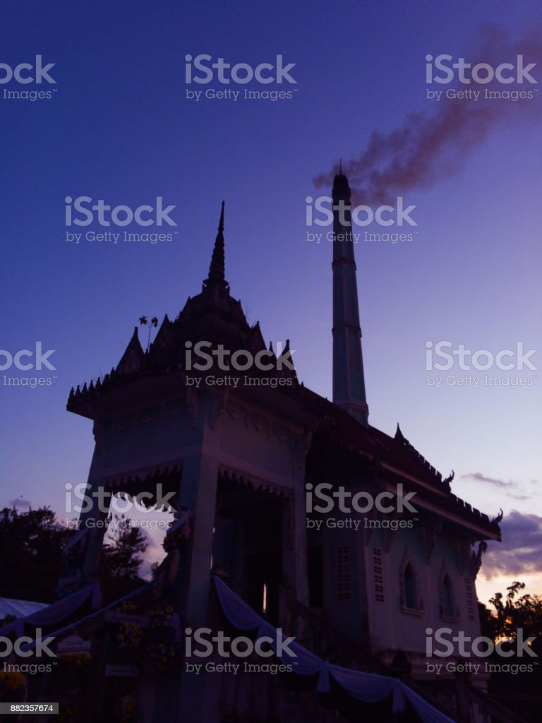 Burning the dead body at crematorium in the temple with firewood in rural Thailand that began at dusk. stock photo