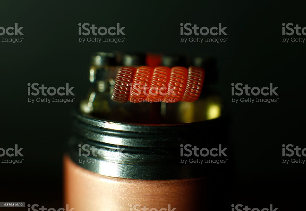 Burning triple staggered fused clapton coil in rebuildable dripping atomizer stock photo