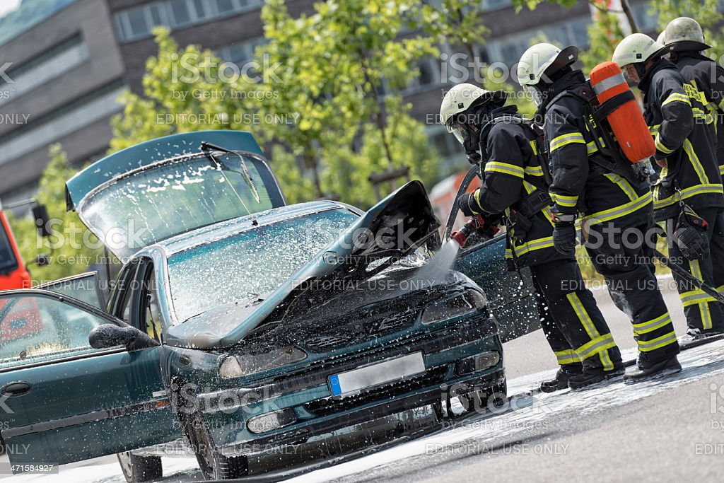 Burning vehicle been put out by firemen in protective clothing royalty-free stock photo