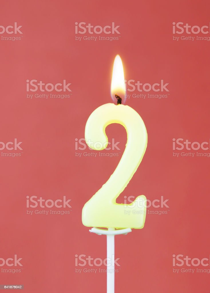Burning Wax Candle As Number Two On Red Background