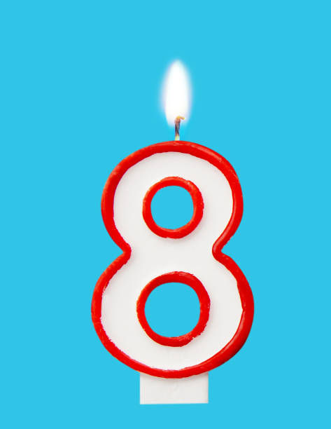 burning wax candle for a birthday cake in the form of number eight. blue background - number 8 stock pictures, royalty-free photos & images