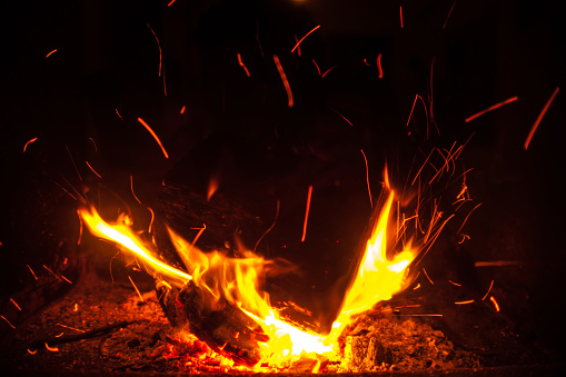 Burning wood flames with sparks in the dark
