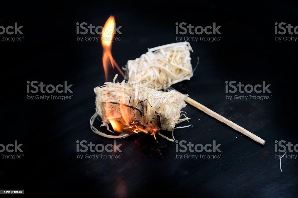 burning wood wool barbecue lighter on a black metal bowl, copy space zbiór zdjęć royalty-free