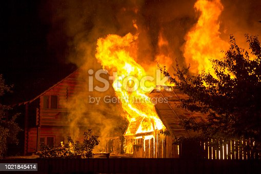istock Burning wooden house at night. Bright orange flames and dense smoke from under the tiled roof on dark sky, trees silhouettes and residential neighbor cottage background. Disaster and danger concept. 1021845414