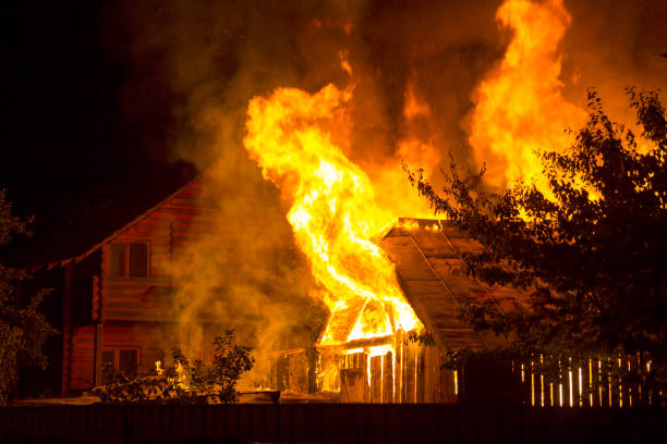 burning wooden house at night. bright orange flames and dense smoke from under the tiled roof on dark sky, trees silhouettes and residential neighbor cottage background. disaster and danger concept. - fuoco foto e immagini stock
