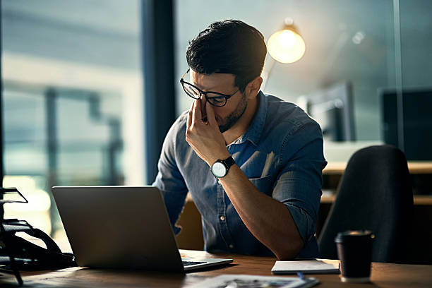 Burnout is killing his career Shot of a young businessman experiencing stress during a late night at work mental burnout stock pictures, royalty-free photos & images