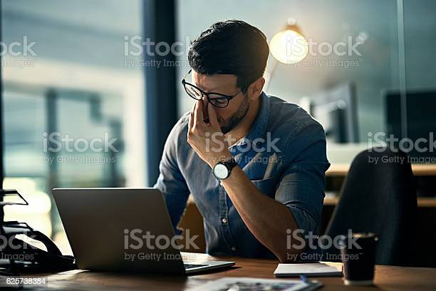Shot of a young businessman experiencing stress during a late night at work