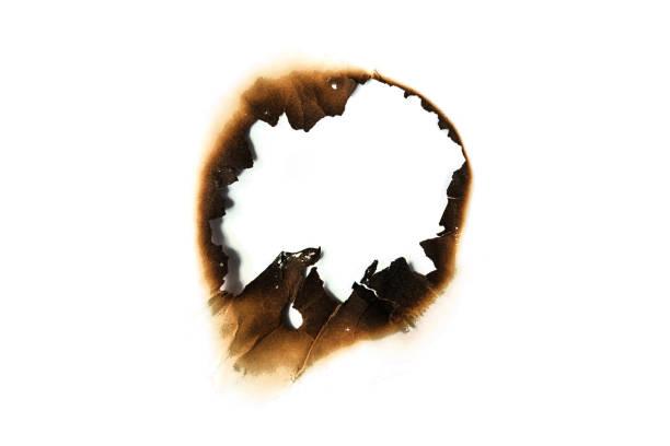 agujero de papel quemaduras en fondos blancos - quemar fotografías e imágenes de stock