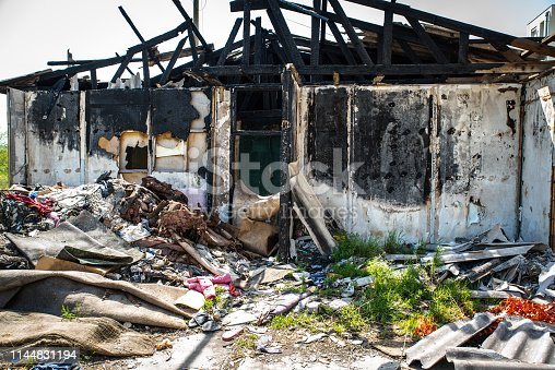 1015604922 istock photo Burnt abandoned wooden barrack with pile of garbage and litter and burned walls 1144831194
