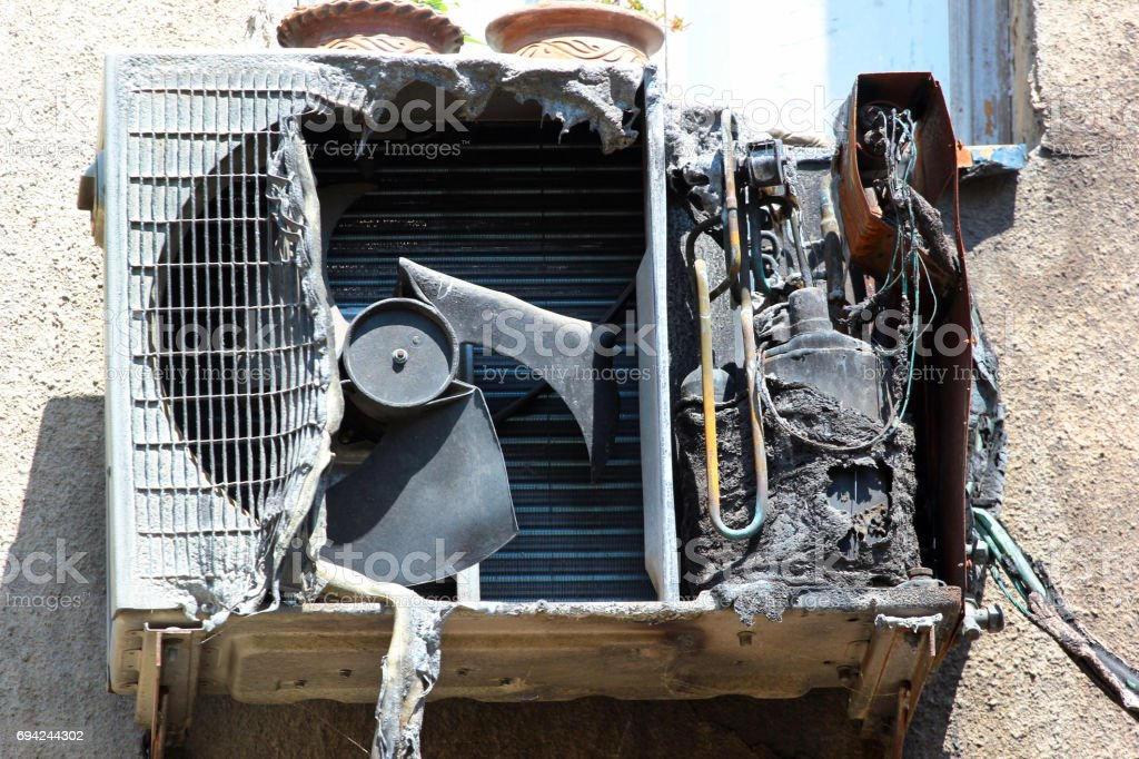 Burnt and charred air conditioner unit after a fire stock photo