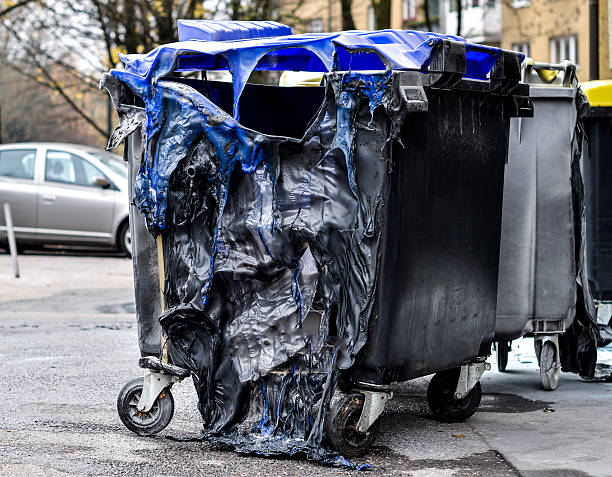 Burnt and melted trash can form a fire. Burnt and melted trash can form a fire. Burned trash in waste container in the city is melted due to hot fire inside. dumpster fire stock pictures, royalty-free photos & images