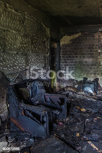 istock Burnt apartment house interior. Burned chair, charred walls 900873566