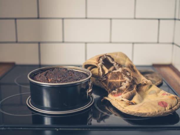 burnt cake and oven glove on cooker - burned cooking imagens e fotografias de stock