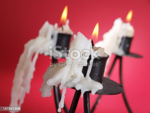 Candlestick with candle isolated on red background