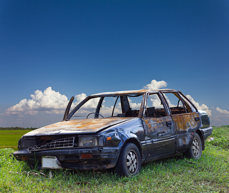 A car accidentally burned in the car due to an accident on the lawn in rural Thailand with a backdrop of clouds.