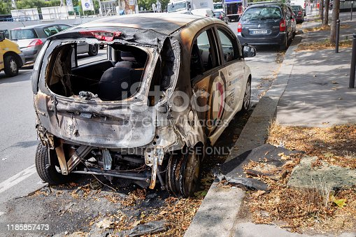 800485914istockphoto Burnt car on the streets of Paris 1185857473