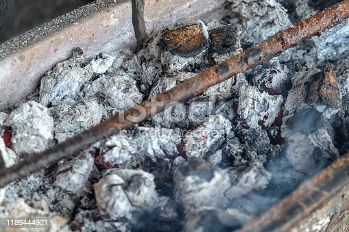 Close up shot of burnt charcoal ash inside a barbecue grill after cooking, a little smoke still appearing from the fire