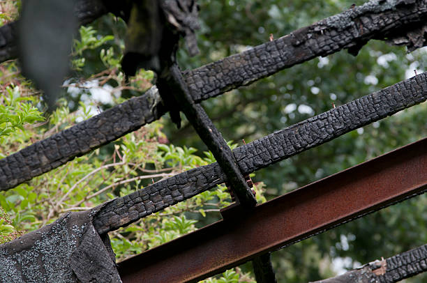 Burnt charred wood remains hanging from structure stock photo