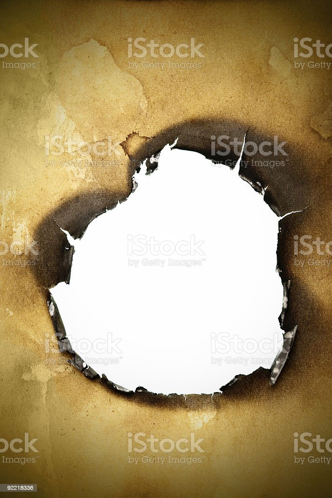 Burnt hole in paper with ashy edges royalty-free stock photo