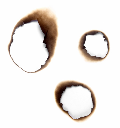 Three different burnt holes in a piece of paper photo. With slight shadow under the edges