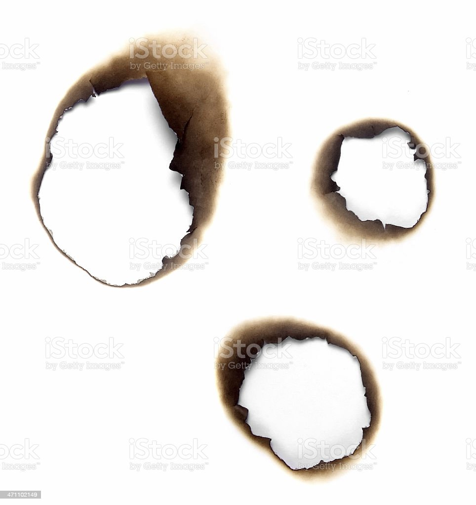 Burnt holes in a piece of paper stock photo