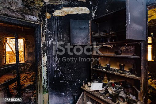 istock Burnt house interior. Burned furniture, kitchen cabinet, charred walls and ceiling in black soot 1078493080