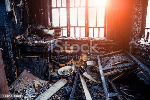 istock Burnt house interior. Burned kitchen, remains of furniture in black soot 1142091409