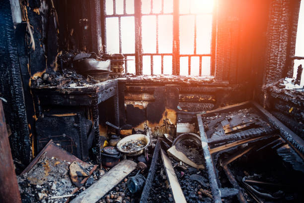 burnt house interior. burned kitchen, remains of furniture in black soot - danneggiato foto e immagini stock