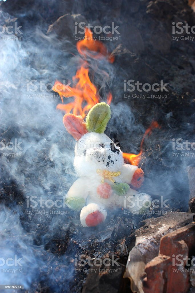 Burnt houses and toy rabbit stock photo